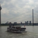 Cruise ship framed by Rhinetrum Observation Tower and Rhine River bridge