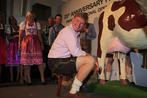 Ernie Els dons the Lederhosen's to milk a mechanical cow during last night's Players Party to help celebrate 25th anniversary of the BMW International Open.  (Photo - Eoin Clarke/www.golffile.ie)