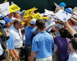 Rory McIlroy surrounded by autograph hunters at the back of the 18th green.