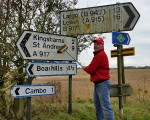 Bernie takes a broom to badly discoloured road signs  opposite good friend  George Morris' Crail abode.