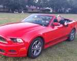 Bernie behind the wheel of a gleaming red Ford Mustang convertible.