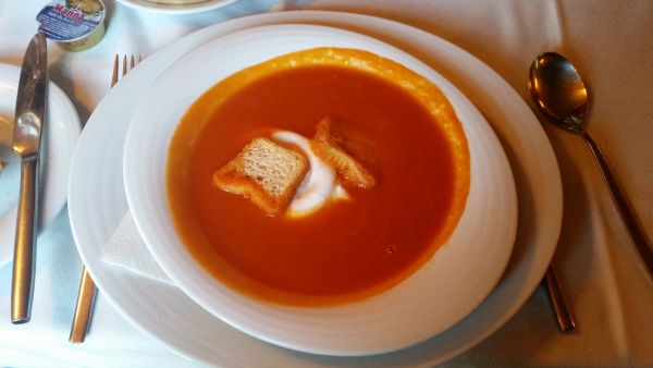 Rich tomato soup with a poached egg .