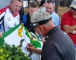 Darren Clarke signs his name under that of Rory McIlroy on a Northern Ireland county flag.