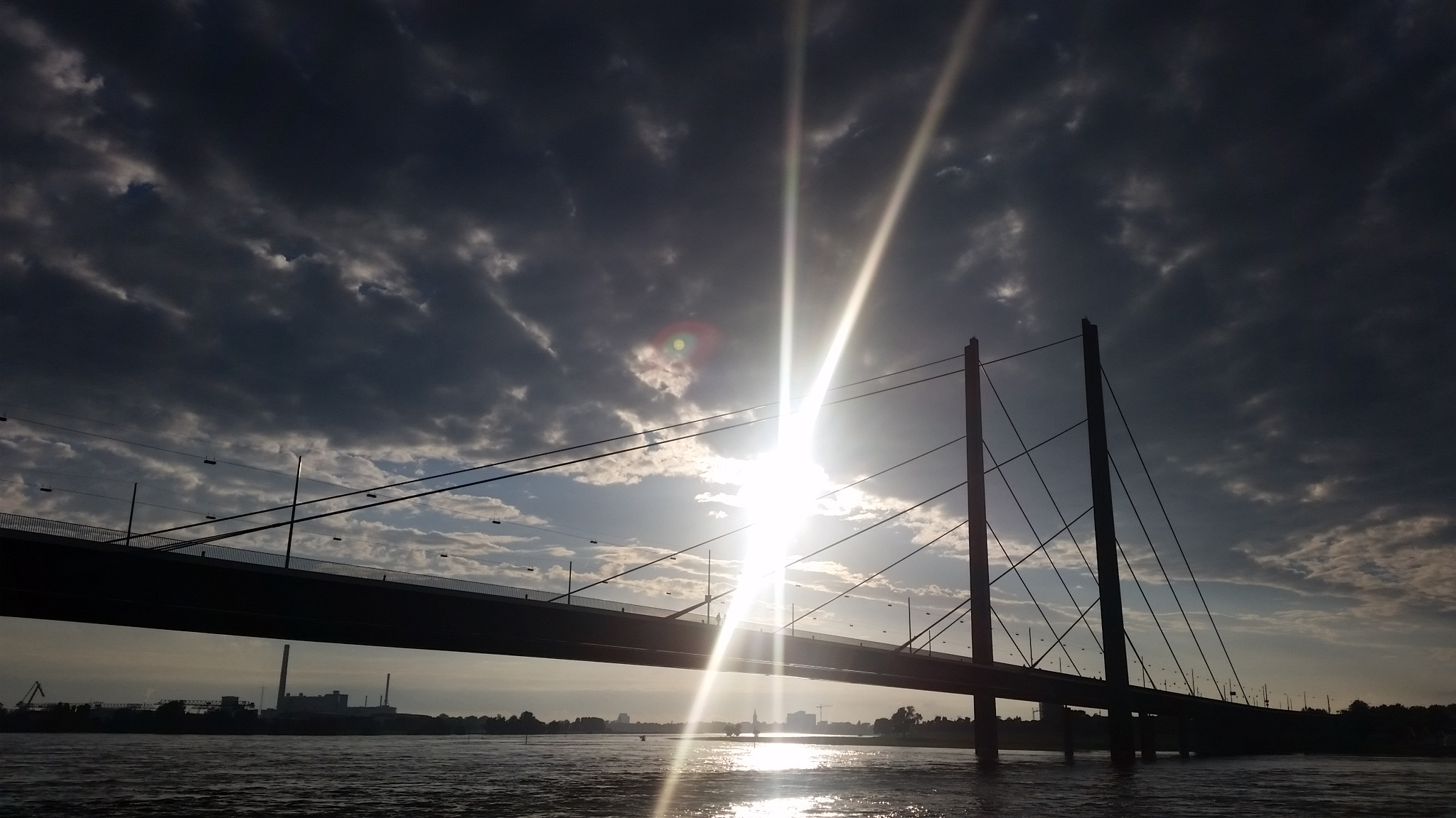 The sun setting over the Oberkassel Bridge at Dusseldorf