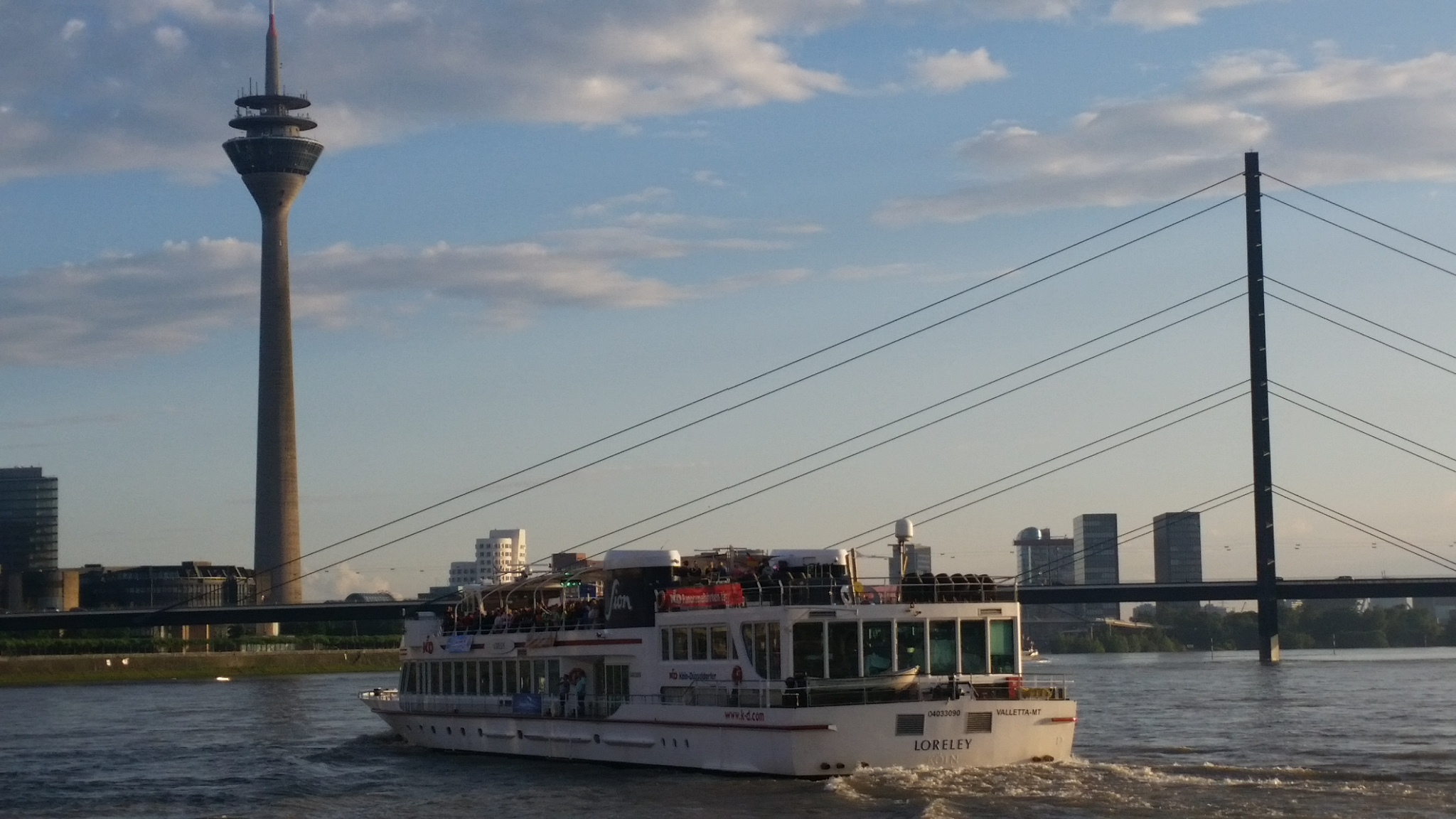 A Rhein River cruise ship in frame between the Rhein Tower and the towers of the Oberkassel Bridge.