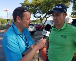 Russell Knox chatting with BBC 5 Live Iain Carter as the England flag  flutters in the background at the Austin Country Club.
